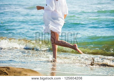 woman run at sand beach by the sea, lower body, sunny summer day