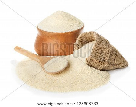 Raw unprepared semolina in bowl and spoon close-up isolated on white background