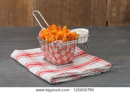 Basket of deep fried sweet potatoes with a buttermilk dill dipping sauce.