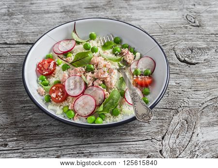 Delicious healthy food - salad with cous cous fresh vegetables and baked salmon. On a light wooden rustic background