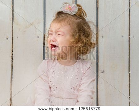 offended little girl weeping with face turned away