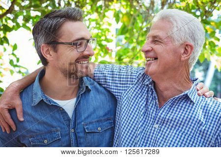 Cheerful father and son with arm around while standing outdoors