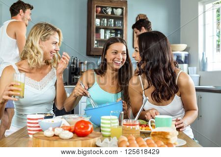 Cheerful young women with male friends cooking together in kitchen at home