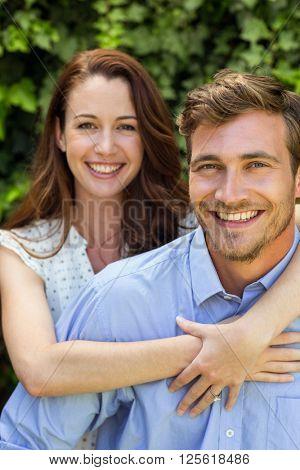 Young smiling woman hugging man at front yard