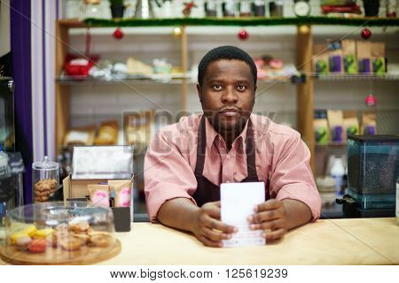 Portrait of a salesman at counter of confectionary