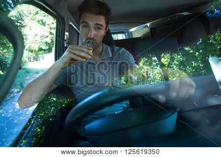 Portrait of slumped man drinking alcohol while driving car