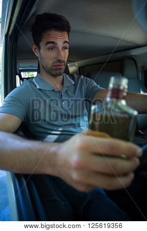 Slumped man with alcohol bottle while driving car