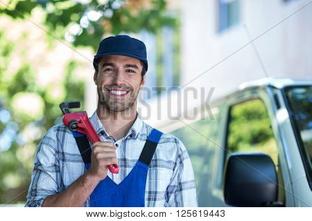 Portrait of happy carpenter holding pipe wrench while standing by van