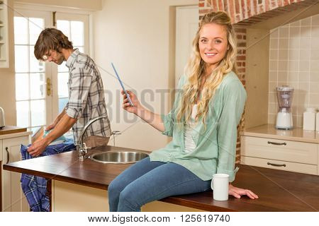 Pretty blonde using tablet while boyfriend ironing a shirt in the living room