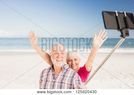 Senior couple taking selfie on the beach