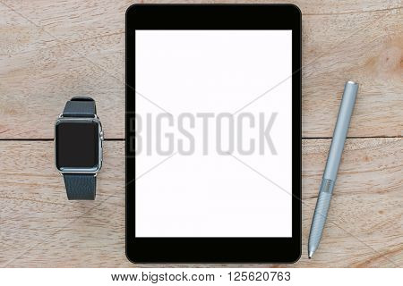 Smart watch with leather bands, black tablet computer with white blank screen and thin-tip stylus pen on wooden background
