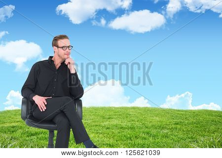 Thoughtful businessman sitting on a swivel chair against blue sky over green field
