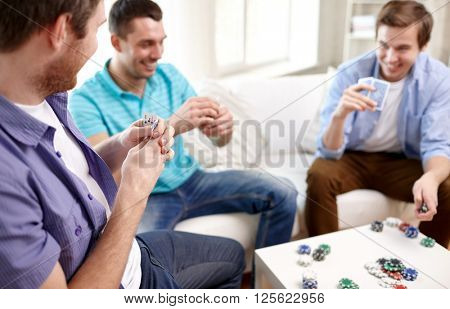 leisure, games, friendship, gambling and entertainment - close up of male friends playing cards at home