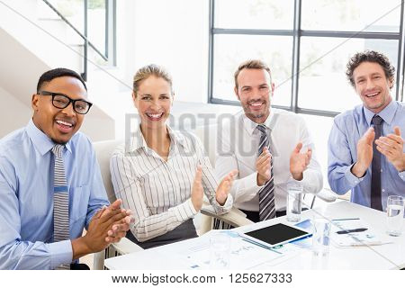 Portrait of businesspeople applauding while in a meeting at office poster