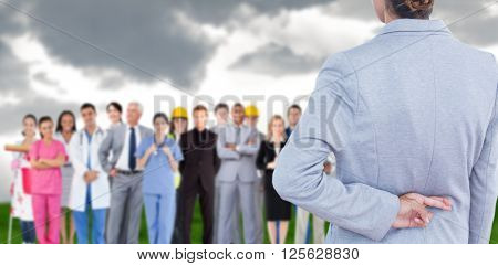 Businesswoman with fingers crossed behind her back over white background against grey sky over field