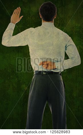 Businessman crossing fingers behind his back against green paint splashed surface