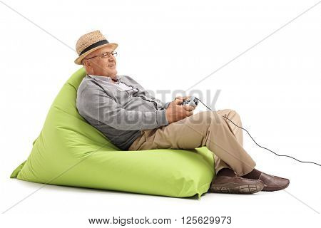 Relaxed mature man sitting on a green beanbag and playing video games with a gamepad isolated on white background