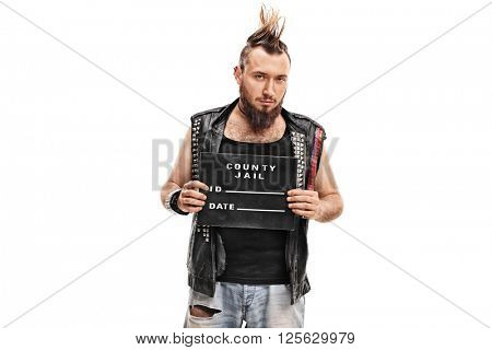 Studio shot of a punk rocker posing for a mug shot with a black plate isolated on white background