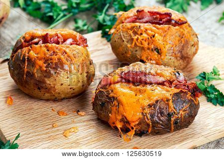 Hot Baked Potato with cheese, bacon and sour cream. on cutting board.