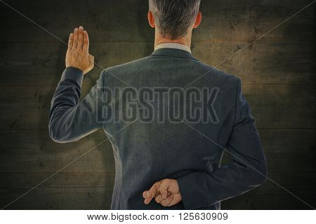 Rear view of businessman taking oath with fingers crossed against bleached wooden planks background