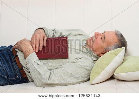 Senior man fell asleep while reading a book.