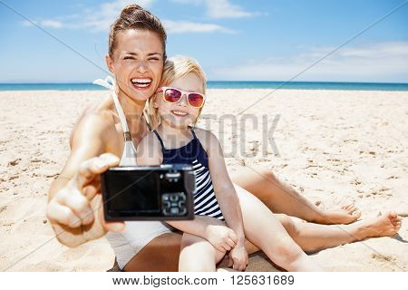 Happy Mother And Child Taking Selfies With Camera At Sandy Beach