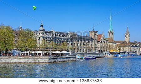 Zurich, Switzerland - 11 April, 2016: view on Stadthausquai quay from the Quaibruecke bridge with the artifcial island Bauschanzli and well-known buildings - Stadthaus Fraumunster and St. Peter Church. Zurich is the largest city in Switzerland.