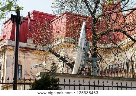 Large parabolic satellite antenna in the backyard of a house