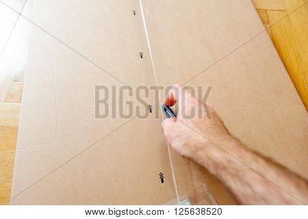 Caucasian man cutting a cardboard box with sharp steel box cutter knife while installing new furniture