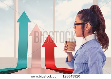 Businesswoman holding disposable cup and looking at wall with notes against bright white room with windows
