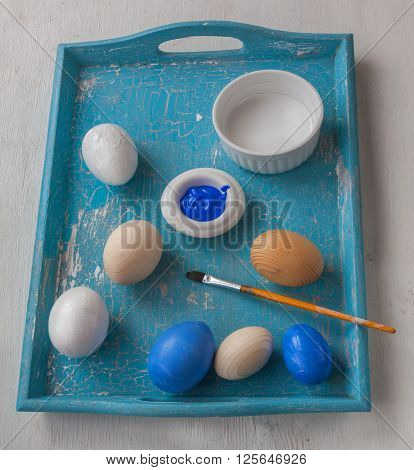 Painting wooden eggs on blue tray for Easter
