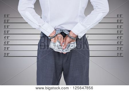 Businessman in handcuffs holding bribe against digitally generated image of height measurement