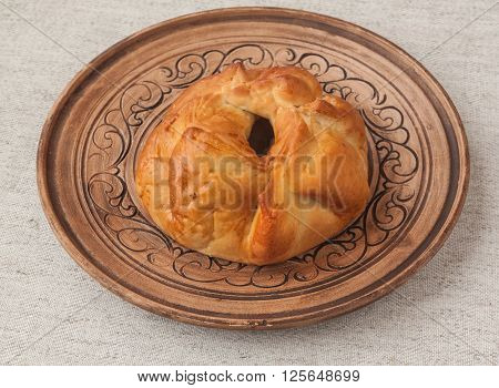 Open bun with meat and onions on a clay plate Ukrainian dish of the Crimean Tatar and Eastern cuisine