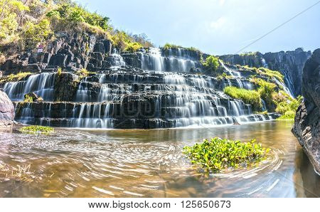Panorama Waterfall in the sun with water flowing down stairs step by creating its folds like silk, beneath the swirl of all scraped up the beauty of nature in Lam Dong, Vietnam