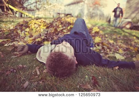 Young boy daydreaming in a pile of fall leaves, slacking on the job, shallow focus