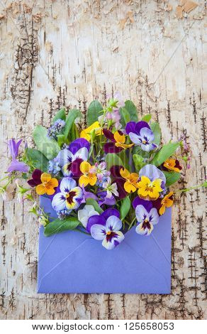 Little bouquet of spring flowers in purple envelope