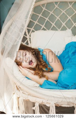 Little girl sleeping in swings. Stock photo.