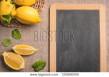 Slices and half fresh juicy lemon with mint leaves and slate board. Top view with copy space.