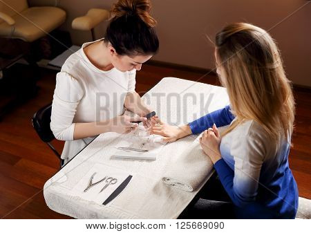 Manicure in a beauty salon for a white table in a dark room is making manicure