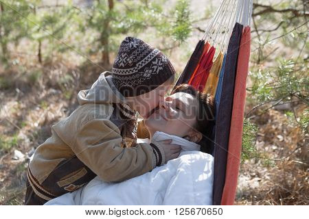 Mother and son relaxing in hammock outdoors