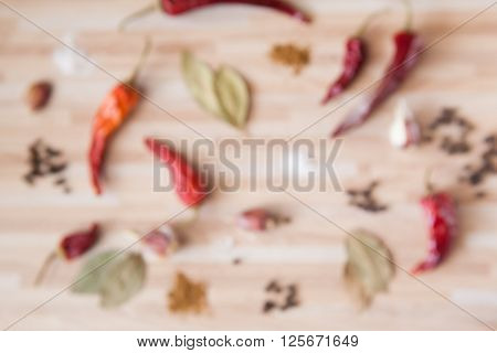 Blured Cusine Background With Chili Pepper, Bay Leaf, Black Pepper, Garlic, Salt, Spices On Light Wo