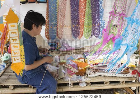 The Man Cutting Paper For Making Colorful Thailand Lanna Flag For Decoration.