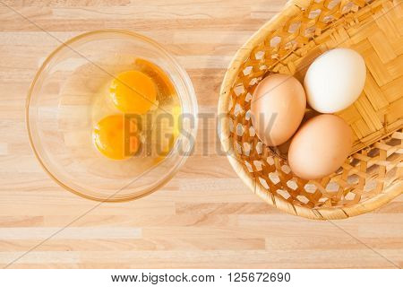 Eggs in braided bucket and raw eggs in glass pialat on light wooden background. Cusine background.