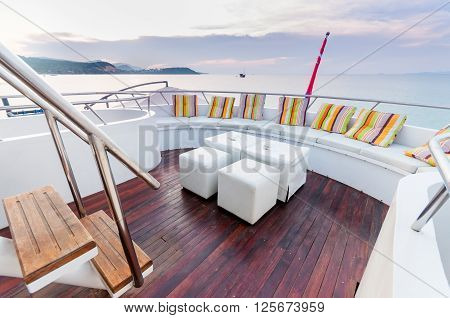Yacht deck setup with white furnitures preparing for a group party.