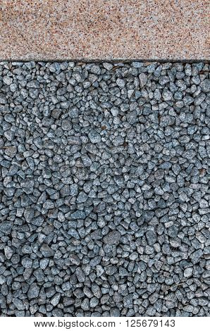 Dark small stones on the ground and concrete