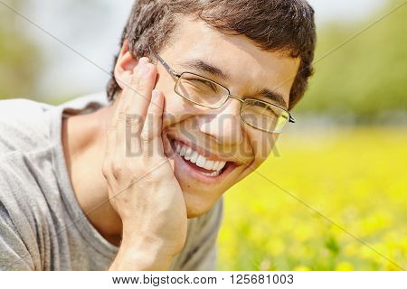 Close up portrait of young hispanic man wearing glasses, lying on grass in spring park outdoors with hand on his head and smiling perfect healthy toothy smile - dentistry or ophthalmology concept