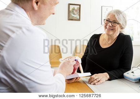 Patient Looking At Male Doctor Explaining Shoulder Rotator Cuff