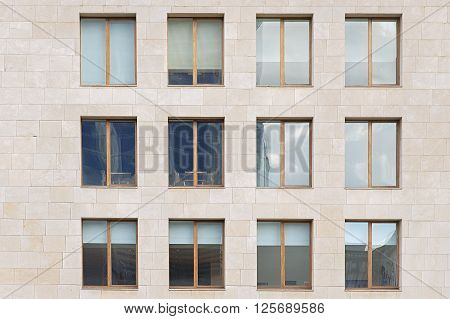 Beige stone wall with many windows close up