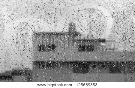 Raindrops on the glass doors with city background.