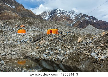 Mountain Expedition Camp Located on Glacier Moraine with Large Ice Crevasse and Melting Lake on Foreground Clothing Hanged on Tent for Drying after Rain